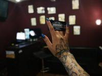 Визитная карточка тату салона в руке