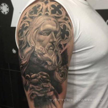 Чёрно-белое религиозное тату на плече мужчины