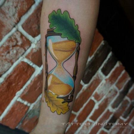 тату женское в стиле ньюскул на руке песочные часы