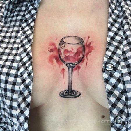 Женское тату в стиле треш полька на груди бокал вина