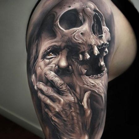 Тату в стиле Black gray на руке череп и лицо