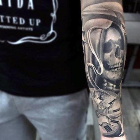 тату в стиле Black gray на руке череп и часы