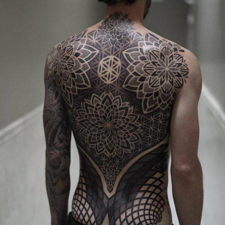 тату мужское в стиле блекворк на спине цветок узор