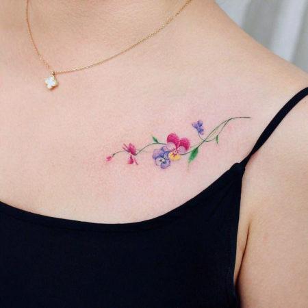 Женское тату в стиле минимализм цветы на ключице