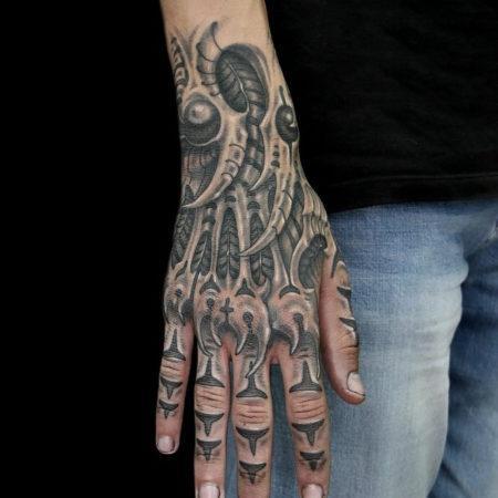 Мужское тату на кисти в стиле биомеханика