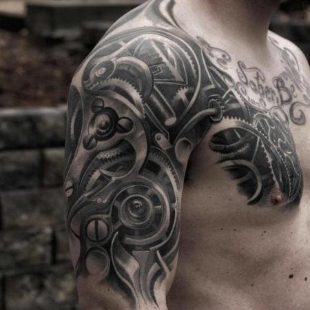 Мужское тату на плече в стиле биомеханика