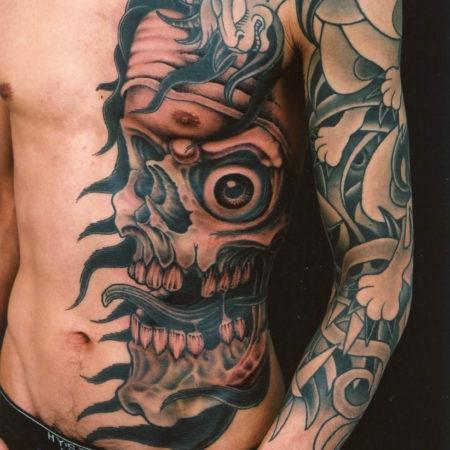 Мужское тату на боку в стиле хоррор череп