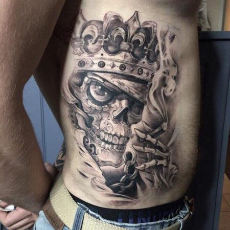 Мужское тату на боку в стиле хоррор череп в короне