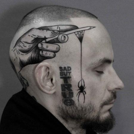 Мужское тату на голове в стиле панк рука насекомое