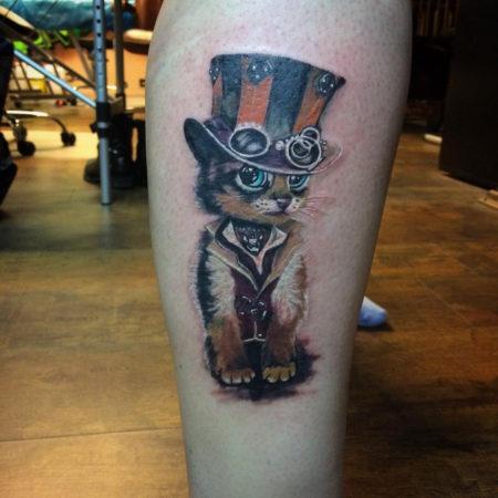 Женское тату в стиле стимпанк на икре кот