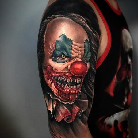 Мужское тату в стиле хоррор на плече клоун
