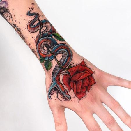 Женское тату на кисти в стиле графика роза и змея