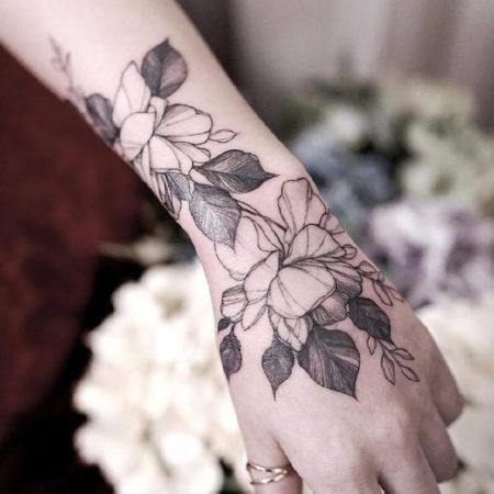 Женское тату на кисти в стиле Linework цветы