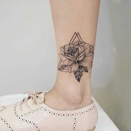 Женское тату на лодыжке в стиле Linework цветок треугольники