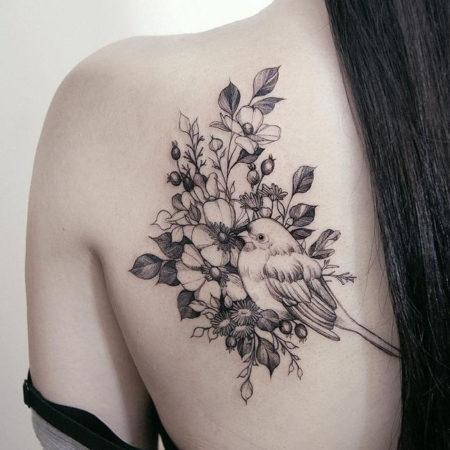 Женское тату на лопатке в стиле Linework цветы и птица