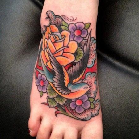 Женское тату на стопе в стиле олд скул птица и цветок