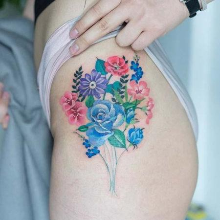 Женское тату на бедре цветы