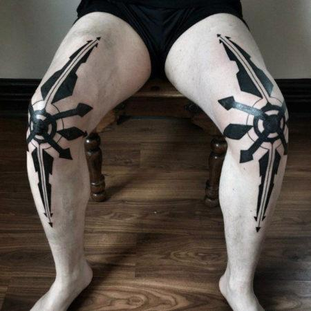 Фото тау в стиле трайбл на коленях мужчины