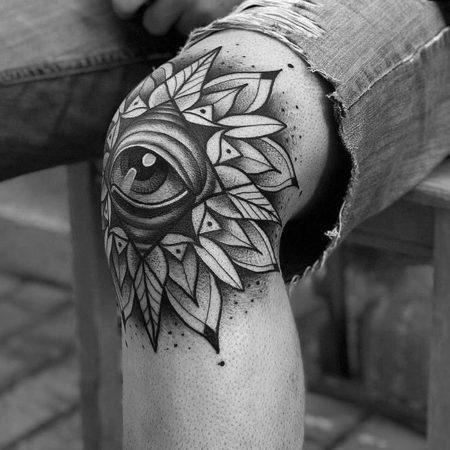 Фото чёрно-белого тату в стиле дотворк на коленях мужчины