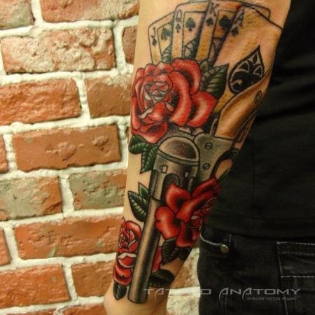 Мужское тату в стиле олд скул розы пистолет карты на предплечье