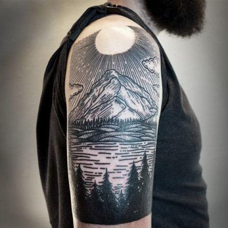 Мужское тату в стиле гравюра на плече пейзаж солнце и лес