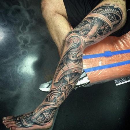 Мужское тату в стиле биомеханика на ноге